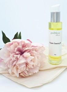 Guiltless Skin's cleaning oil, which is pal yellow in colour, standing on an organic cloth with a pink flower on the left.