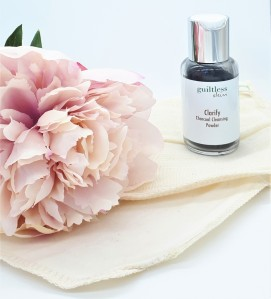 Guiltless Skin's charcoal powder in a glass bottle to the right of the photo. The bottle is standing on an organic cloth next to a pink flower.