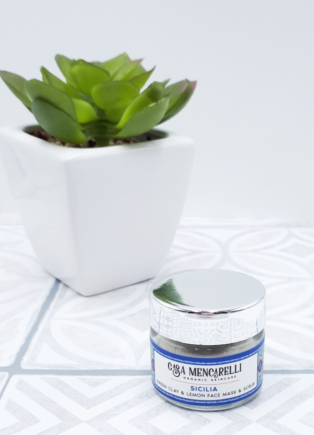 A small glass jar with a silver lid standing on grey and white Moroccan tiles with a white background. In the background there's also a small green plant in a white pot.