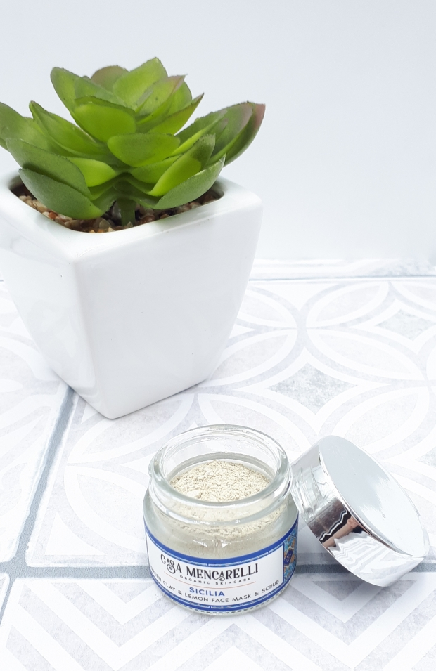 A small glass jar with no lid stands on grey and white Moroccan tiles. The jar contains the clay mask powder which is off-white colour and the lid is propped up against the right hand side of the jar. In the background there's also a small green plant in a white pot.