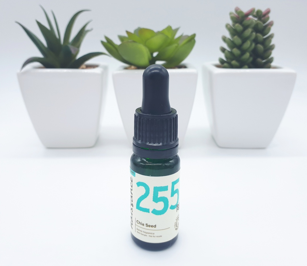 A dark green dropper bottle with a cream label with black and bright blue writing stands on a white backdrop. In the background are 3 different green succulent plants each in their own white square pot.