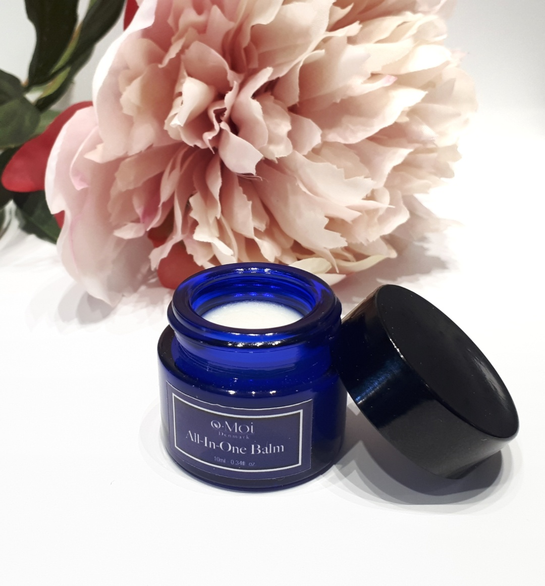 A small blue jar with a dark blue label stands on a white background in front of a pink flower. The lid is leaning up against the jar so the white balm inside is exposed.