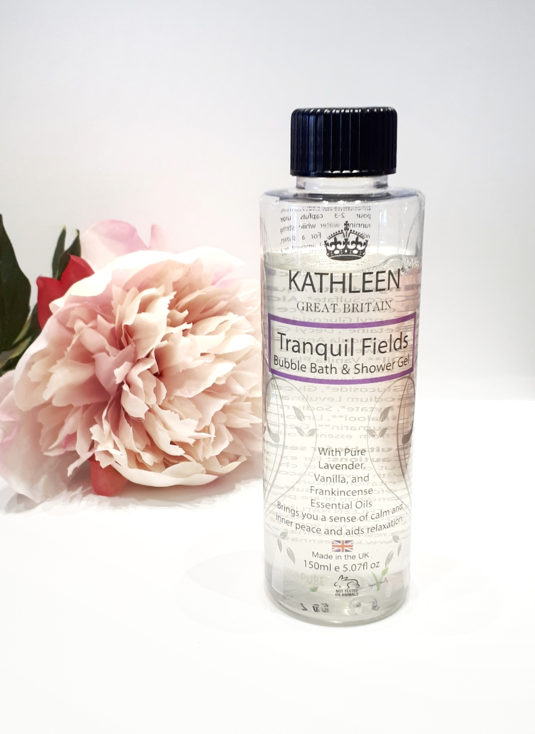 A clear bubble bath bottle stands on a white background next to a pink flower. The bottle has a black cap, with black writing.