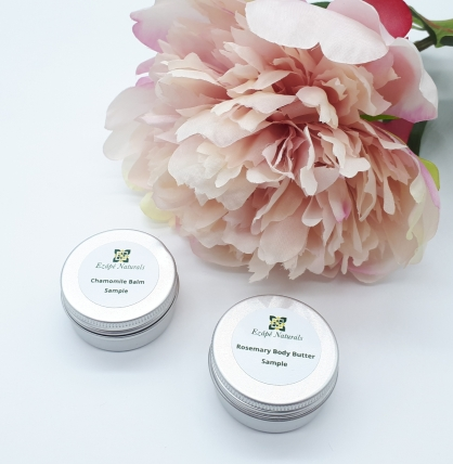 Two small silver tins on a white background next to a pink flower. Each tin has a white label with logo and black writing on it.