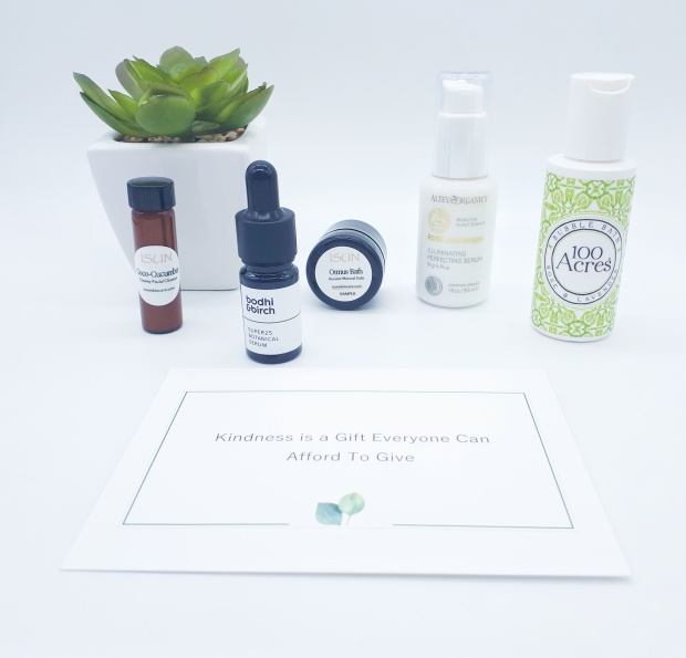 All the products are lined up on a white background. On the left, slightly behind the products is a green plant in a white square pot.