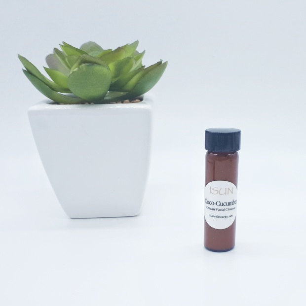 A small brown bottle with a white circle label is standing on a white background. On the left, slightly behind the bottle is a green plant in a white square pot.