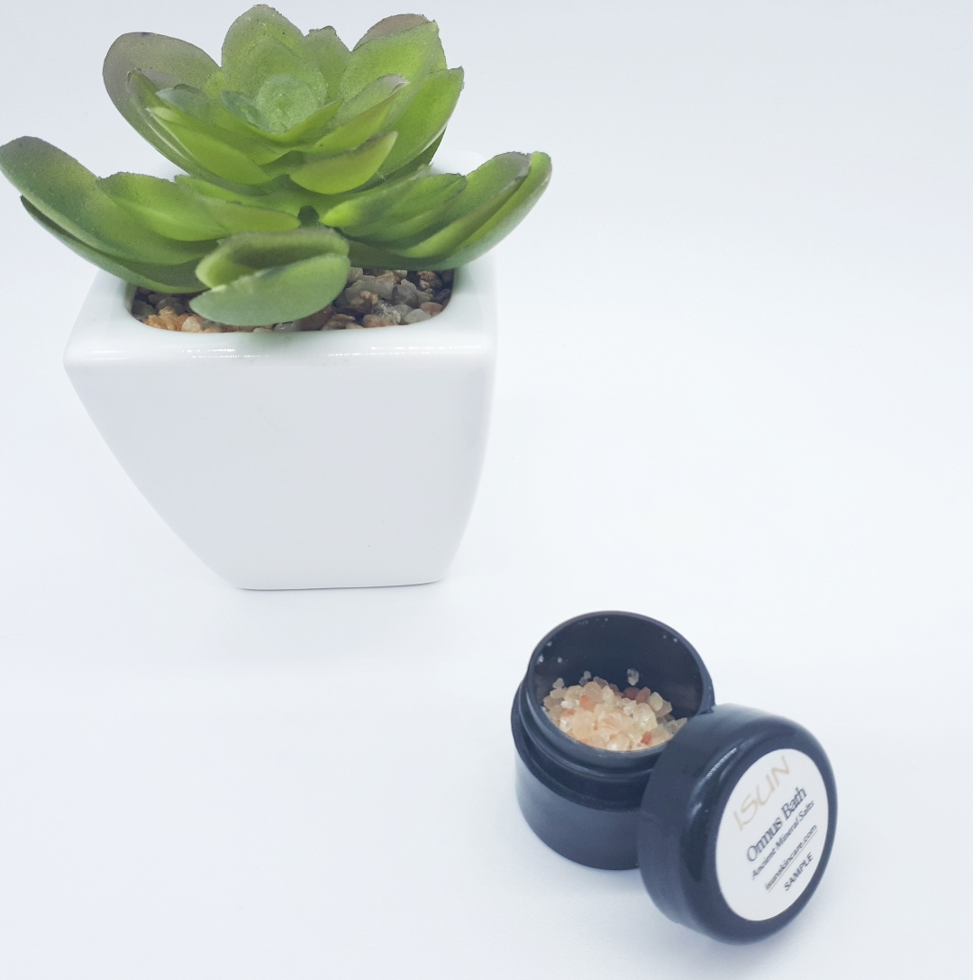 A small black pot containing amber and orange bath salts stands on a white background. On the left, slightly behind the pot is a green plant in a white square pot.