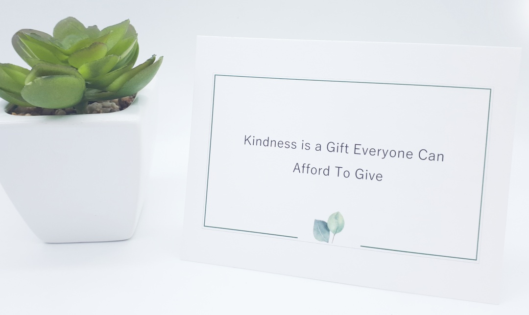 A white postcard with the words 'Kindness is a gift everyone can afford to give' is standing on a white background. On the left, slightly behind the card is a green plant in a white square pot.