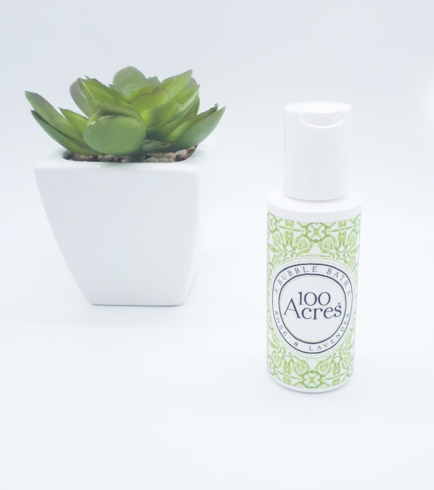 white plastic bottle with a a green and white decorative label featuring black writing is standing on a white background. On the left, slightly behind the bottle is a green plant in a white square pot.