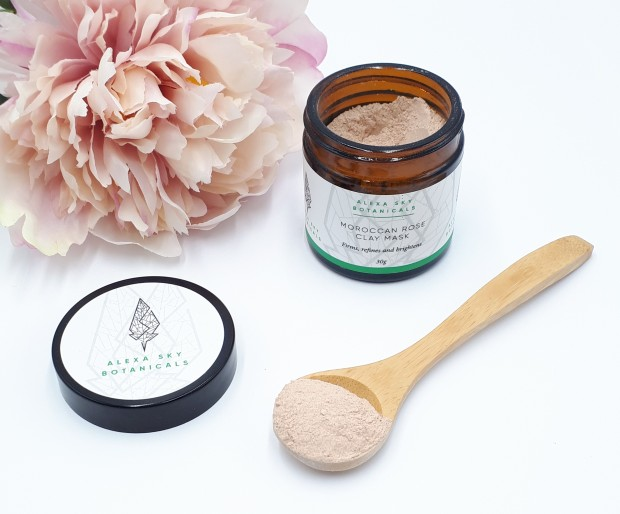 A open jar on a white background next to a pink peony. The jar lid is in front to the left and a small wooden spoon, with some face mask powder on it, lies diagonally on the right in fro