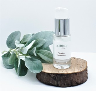 Timeless Moisturiser standing on a log slice with frosted foliage to the side and overlapping the wood.