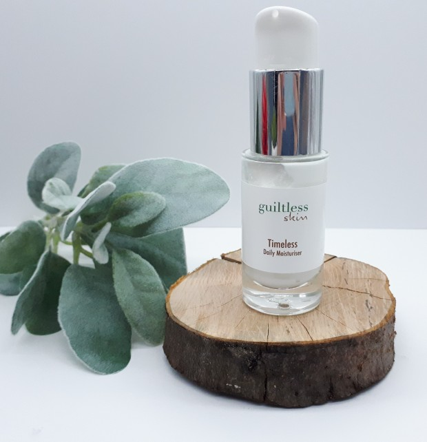 Timeless Moisturiser standing on a log slice with frosted foliage to the side