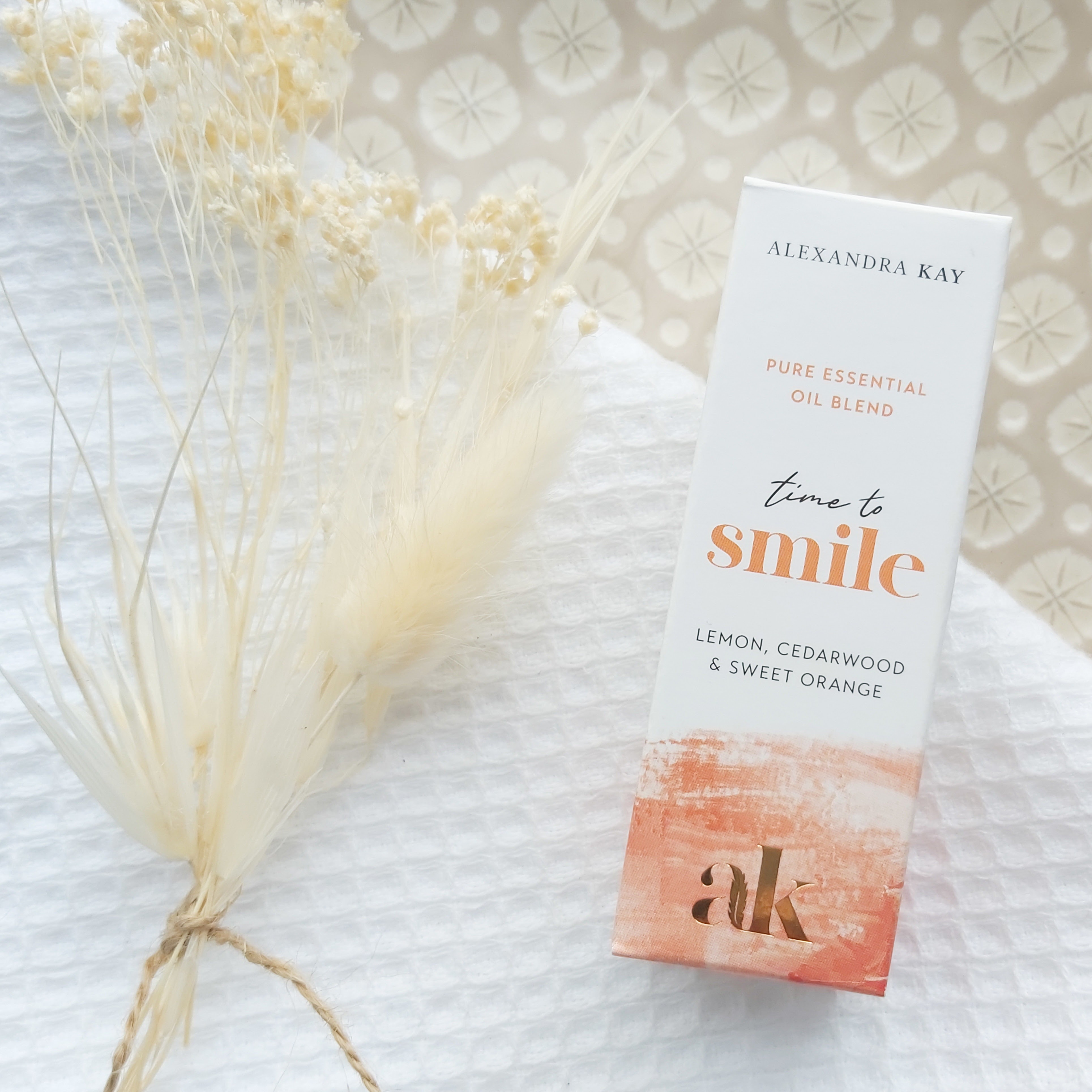 Green People's Alexandra Kay Wellness Time to Smile Essential Oil Box on a plate with dried flowers. Review by Beauty Folio