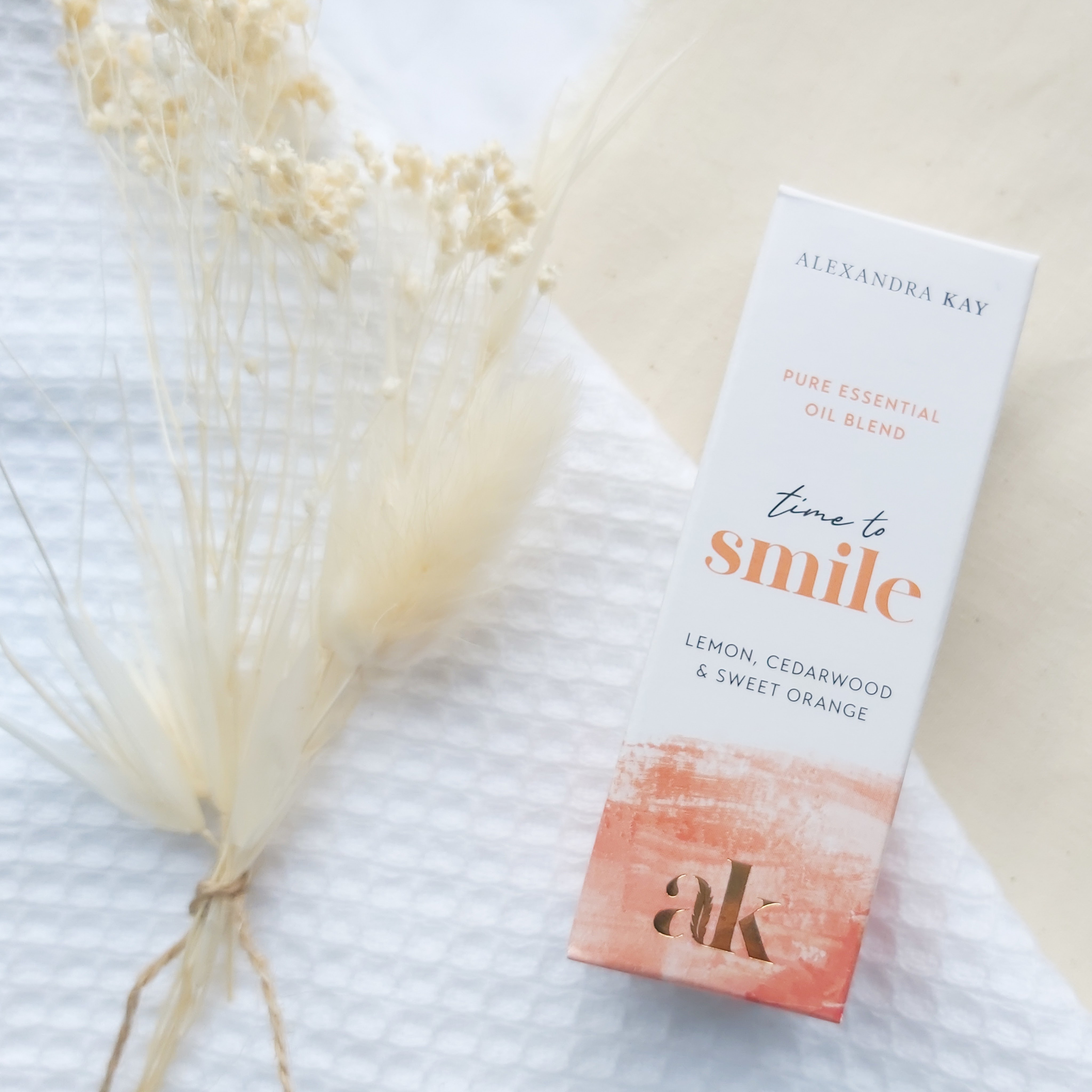 Green People's Alexandra Kay Wellness Time to Smile Essential Oil Box on a white flannel and linen cloth with dried flowers. Review by Beauty Folio