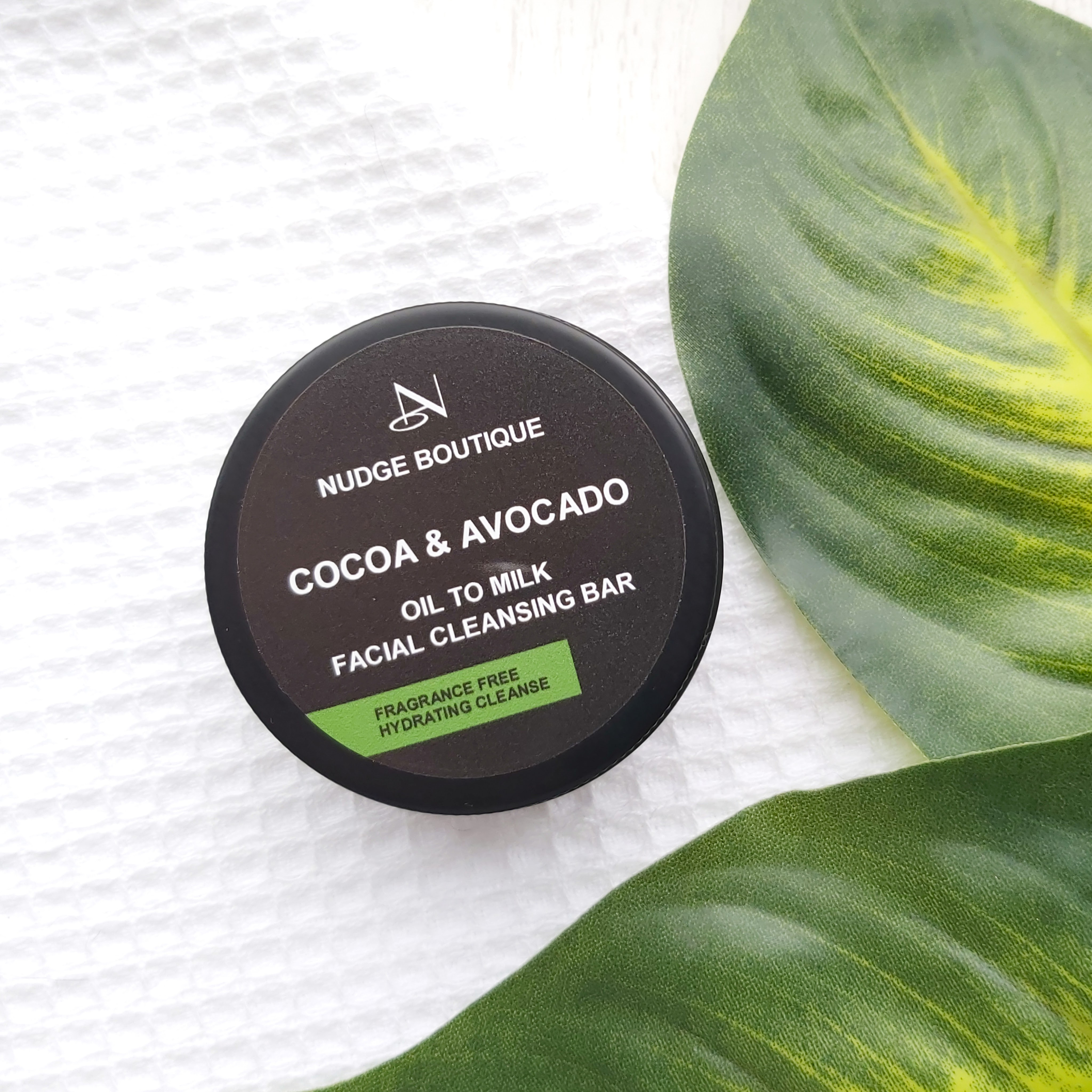 Nudge Boutique Cocoa & Avocado Oil to Milk Cleansing Bar in a black aluminium tin on a waffle flannel and green leaves to the side - Review by Beauty Folio