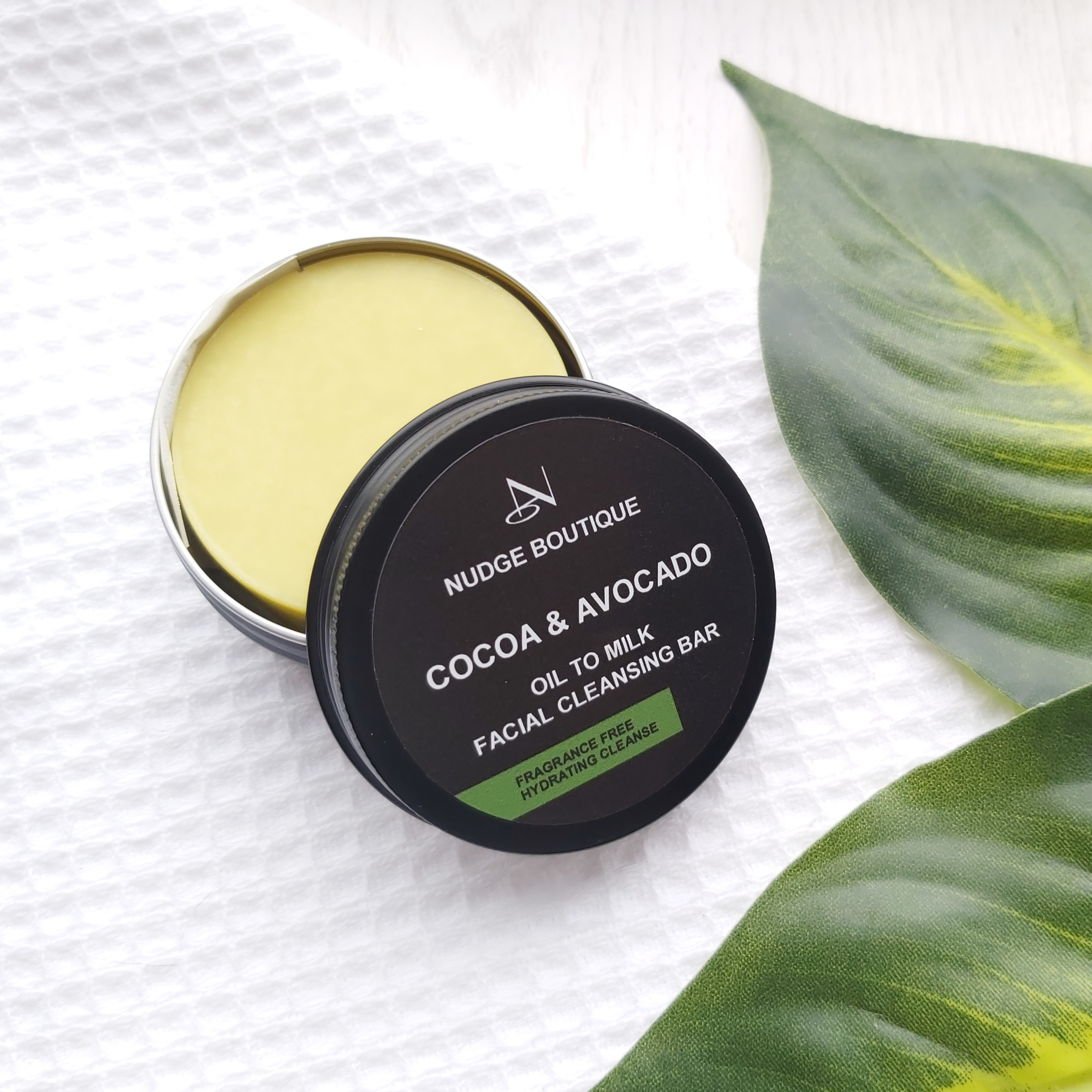 Nudge Boutique Cocoa & Avocado Oil to Milk Cleansing Bar in a black aluminium tin, open with the cleansing bar partially exposed. The tin is sat on  on a waffle flannel and green leaves to the side - Review by Beauty Folio