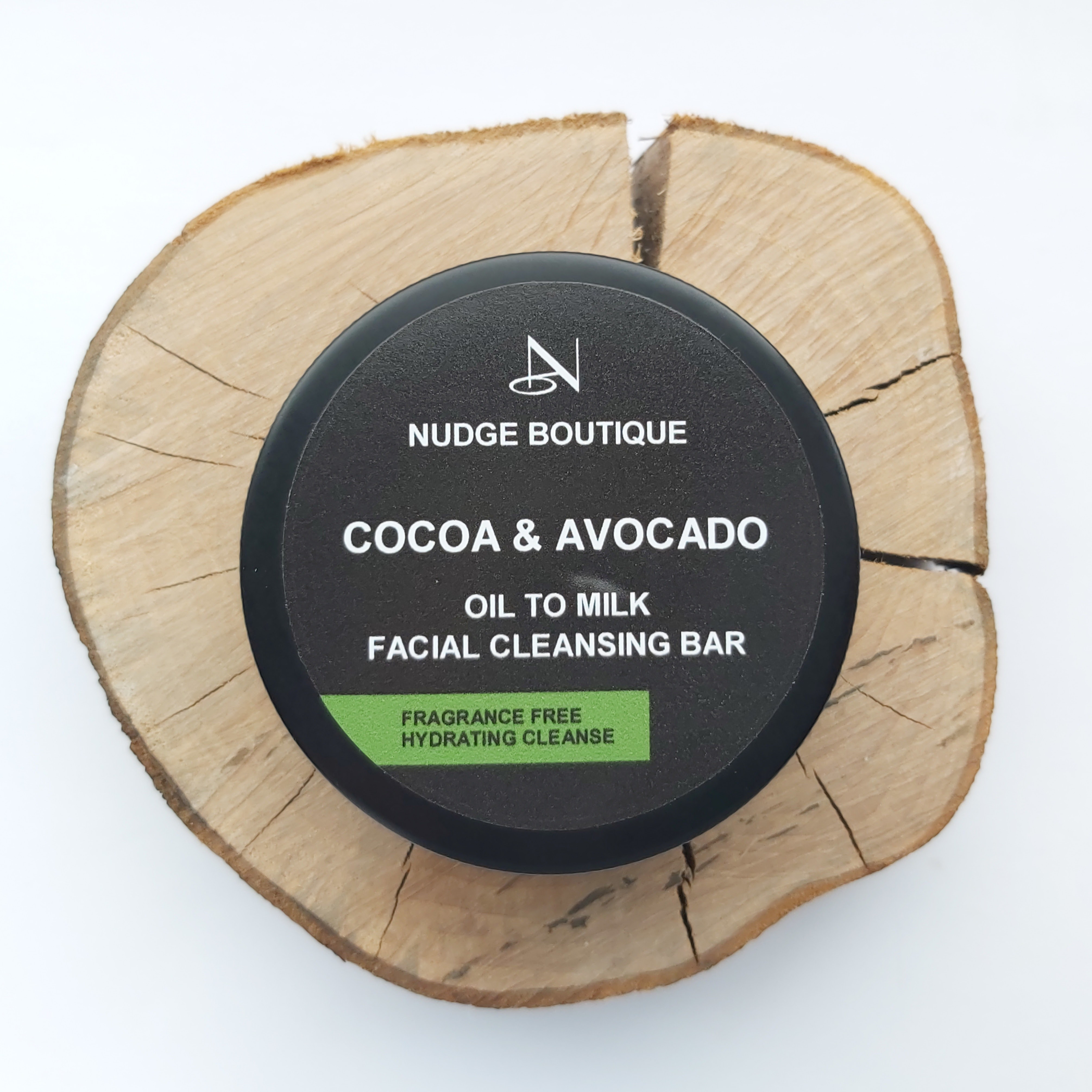 Nudge Boutique Cocoa & Avocado Oil to Milk Cleansing Bar in a black aluminium tin on a wooden slice and white background - Review by Beauty Folio