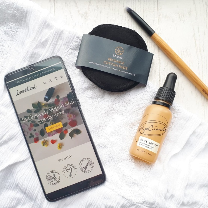 A photo of the website on my smart phone laid next to a Flawless make-up brush, Moonie Reusable Makeup Pads and Upcircle Serum - Review by Beauty Folio