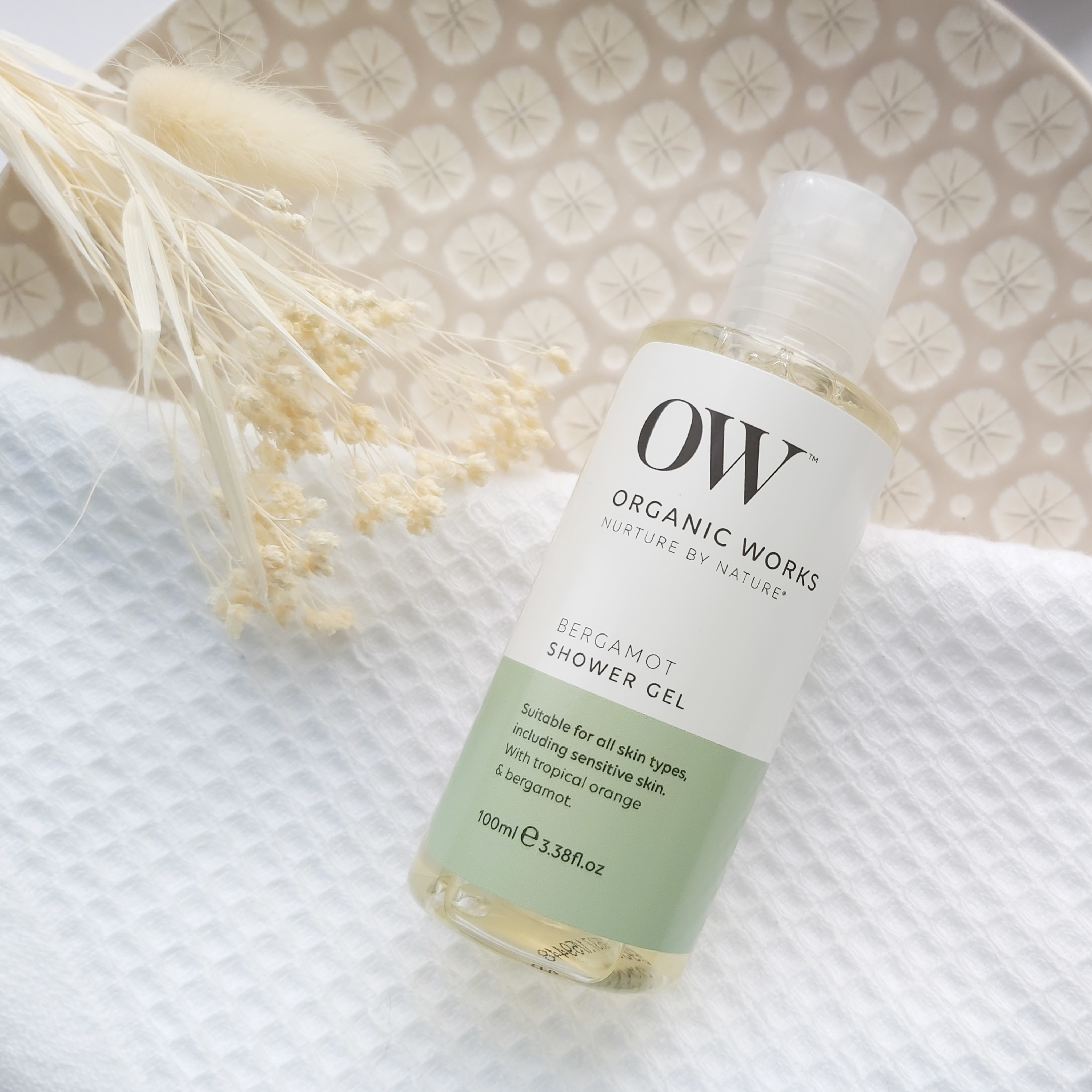 Organic Works bergamot shower gel featured in The Natural Beauty Box May 2021 on a patterned plate, waffle white towel and natural foliage - Review by Beauty Folio