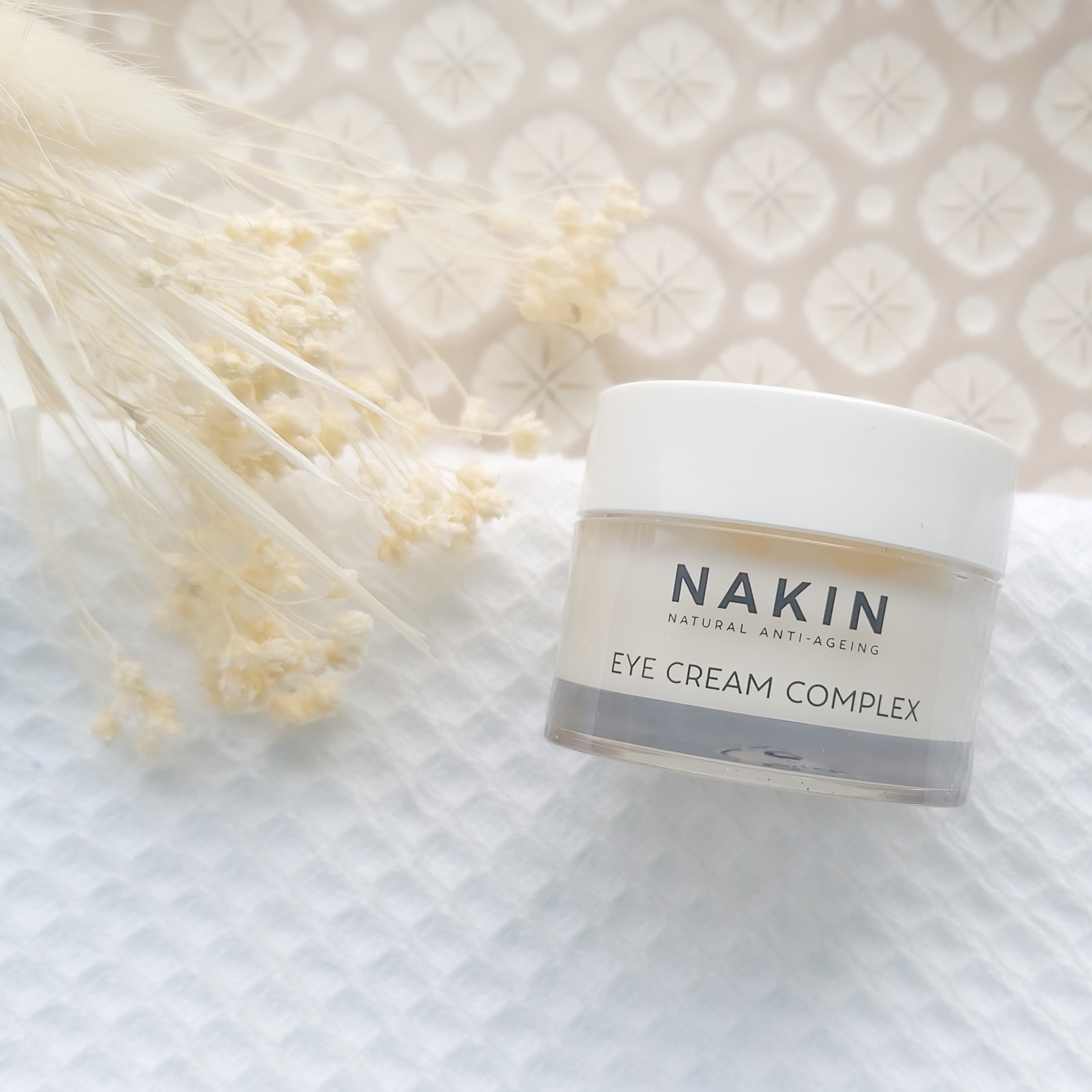 Nakin Skincare Eye Cream Complex featured in The Natural Beauty Box May 2021 on a patterned plate, waffle white towel and natural foliage - Review by Beauty Folio