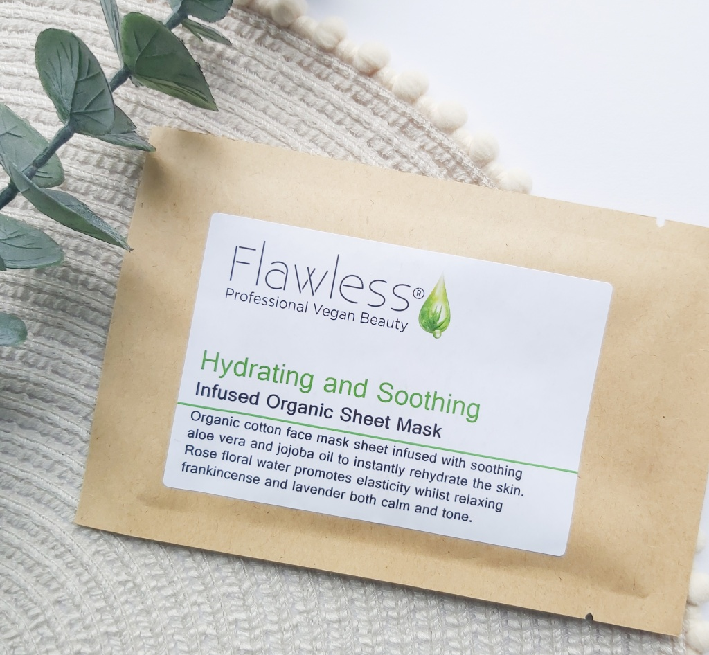 Flawless Organic Cotton Sheet Mask in its brown paper packaging on a beige place mat with pom pom edge and a eucalyptus stem. A Plastic Free Green Beauty Guide by Beauty Folio highlighting plastic pollution and plastic free beauty from Lovethical.