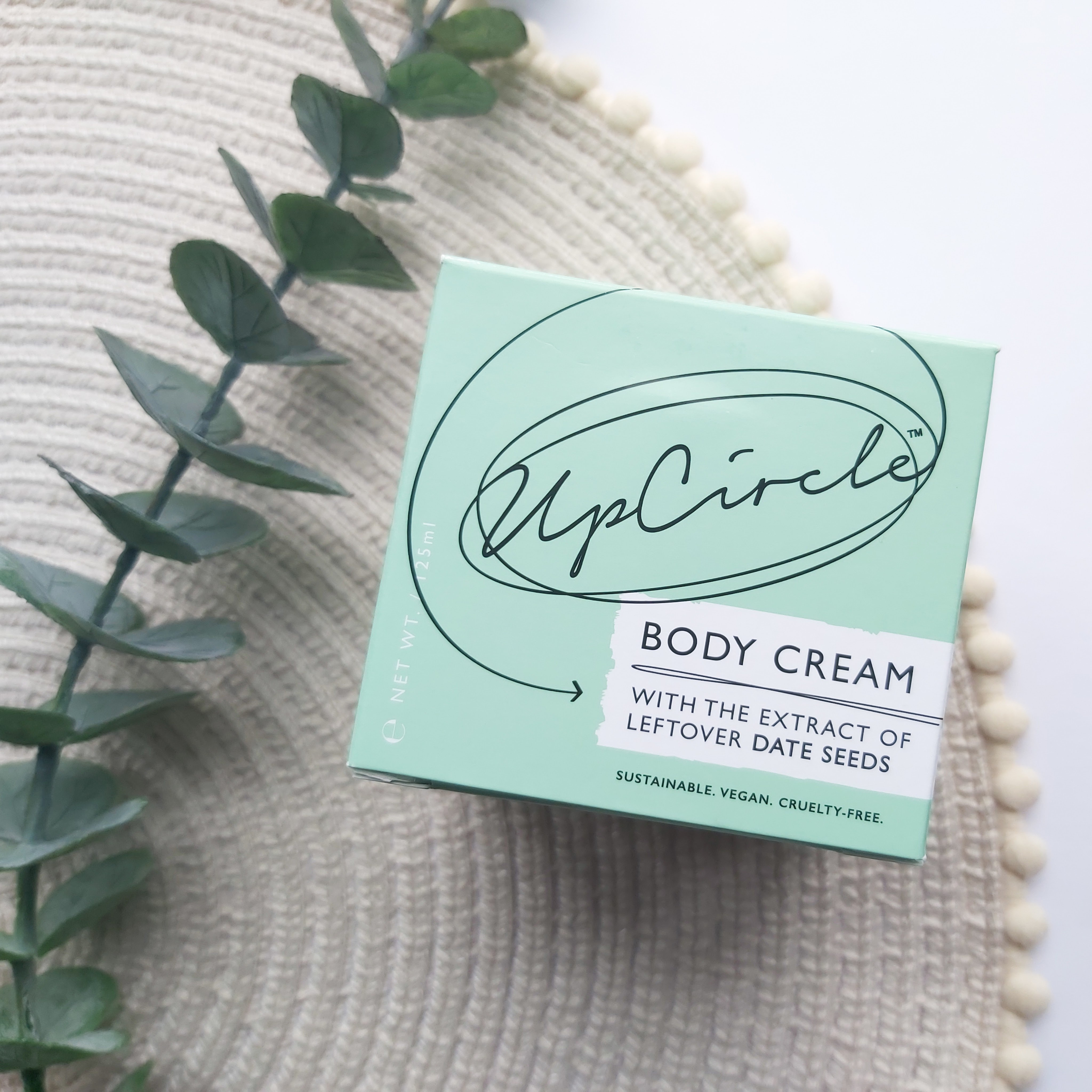 Upcircle's Body Cream in a green outer box on a beige place mat with pom pom edge and a eucalyptus stem. A Plastic Free Green Beauty Guide by Beauty Folio highlighting plastic pollution and plastic free beauty from Lovethical.