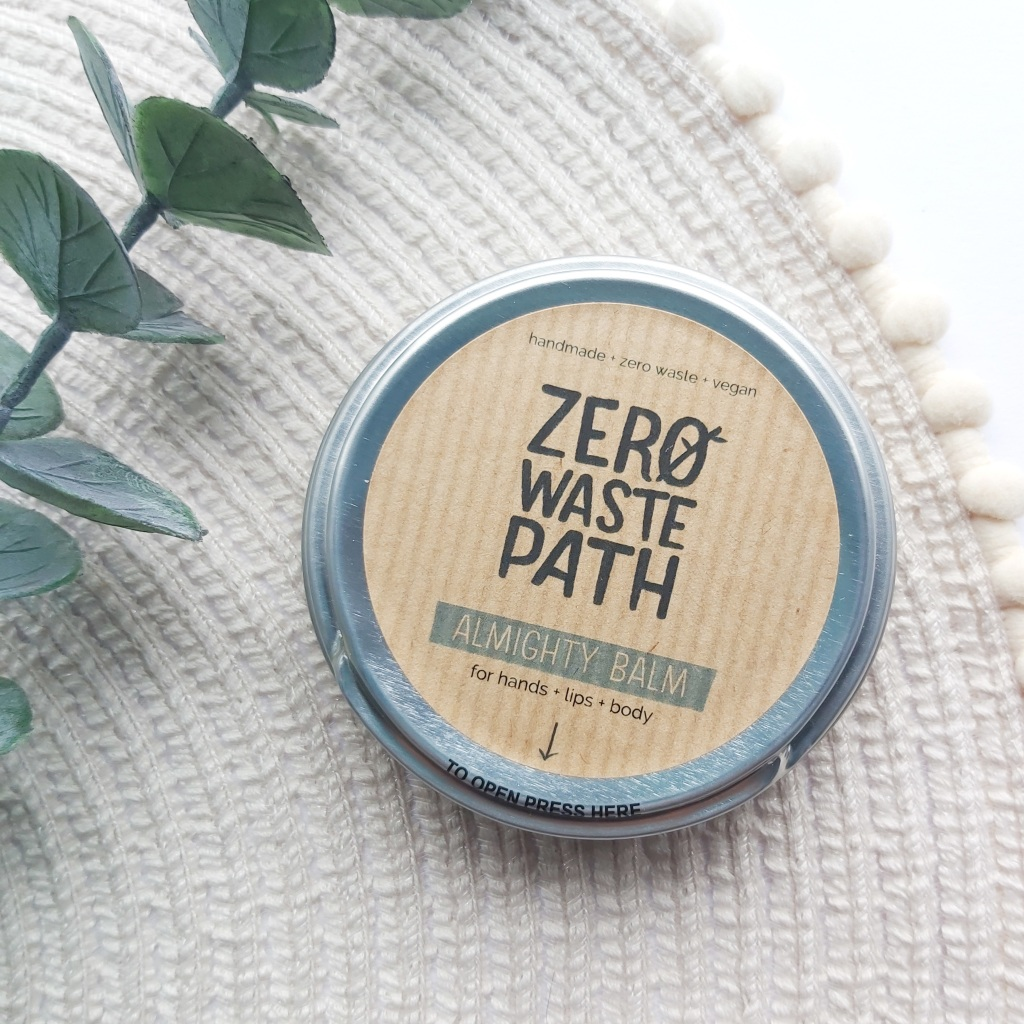 Zero-Waste Path's Almighty Balm in a silver tin on a beige place mat with pom pom edge and a eucalyptus stem. A Plastic Free Green Beauty Guide by Beauty Folio highlighting plastic pollution and plastic free beauty from Lovethical.