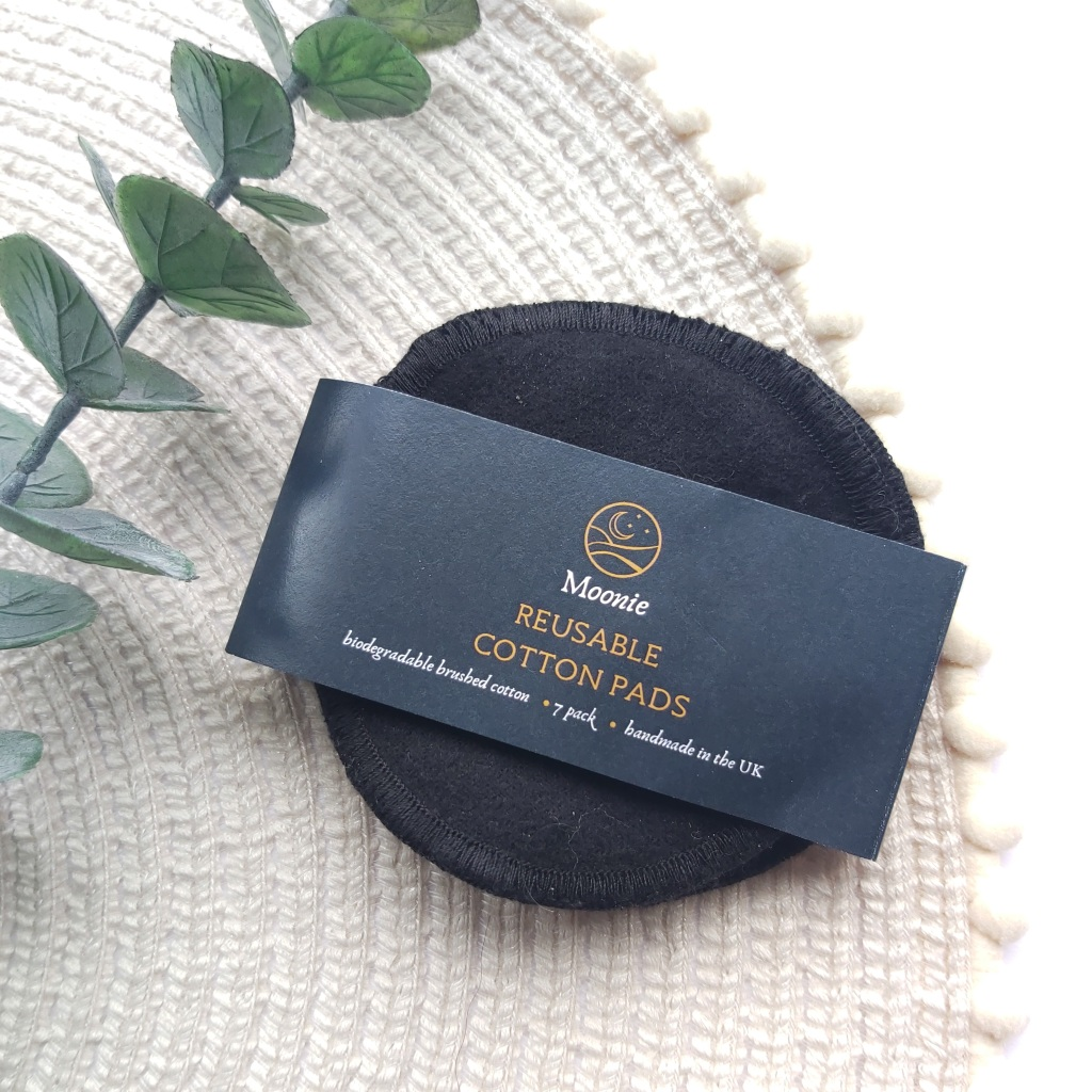 A pack of Moonie Reusable Black cotton pads on a beige place mat with pom pom edge and a eucalyptus stem. A Plastic Free Green Beauty Guide by Beauty Folio highlighting plastic pollution and plastic free beauty from Lovethical.