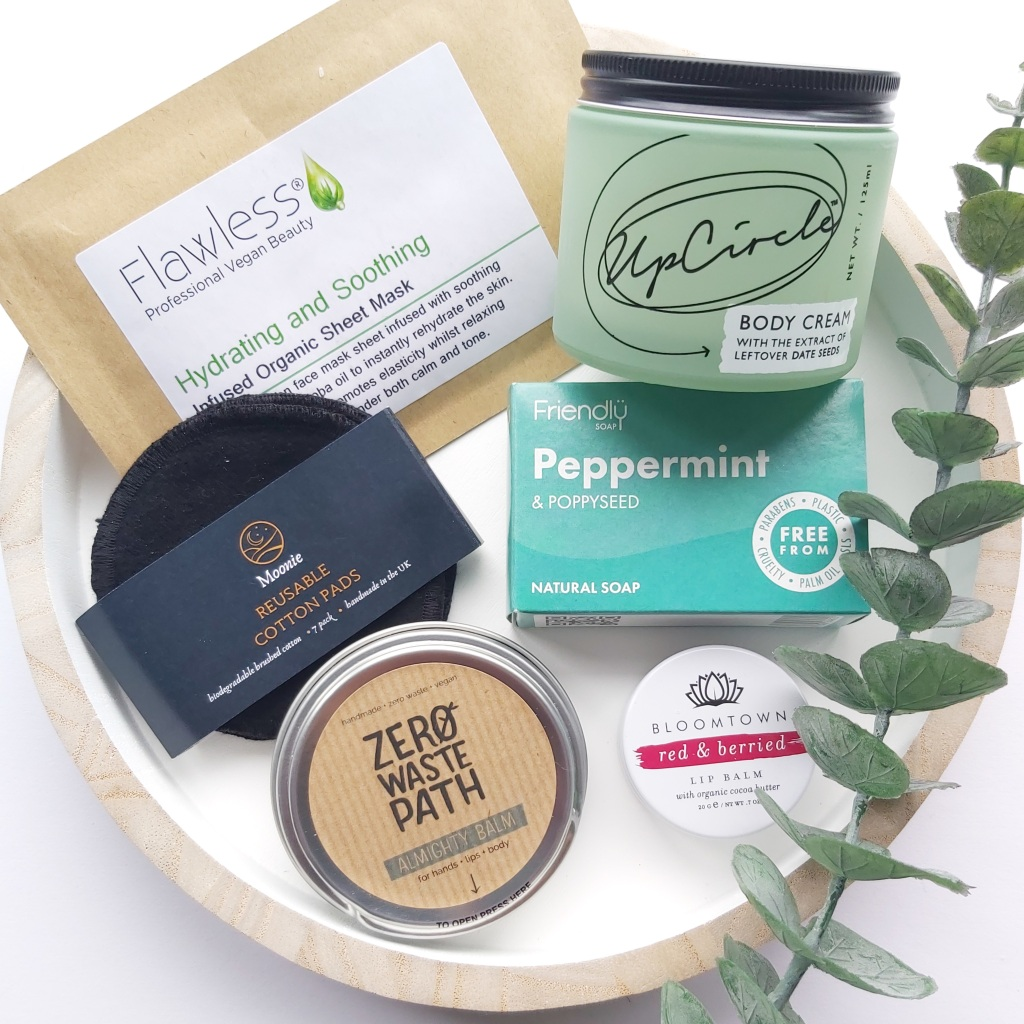 All the plastic free items mentioned on a white tray with wooden edge and a eucalyptus stem. A Plastic Free Green Beauty Guide by Beauty Folio highlighting plastic pollution and plastic free beauty from Lovethical.