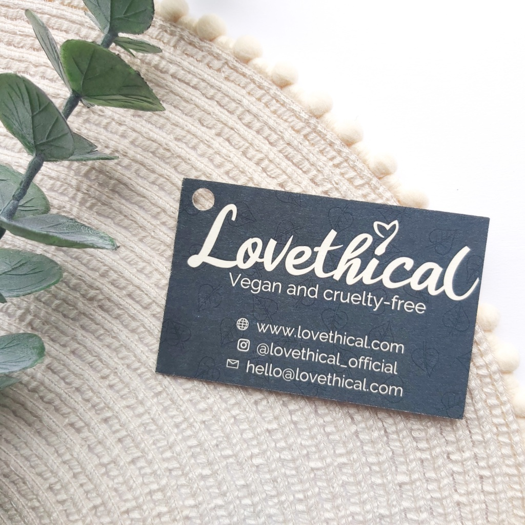 Lovethical business card on a beige place mat with pom pom edge and a eucalyptus stem. A Plastic Free Green Beauty Guide by Beauty Folio highlighting plastic pollution and plastic free beauty from Lovethical.