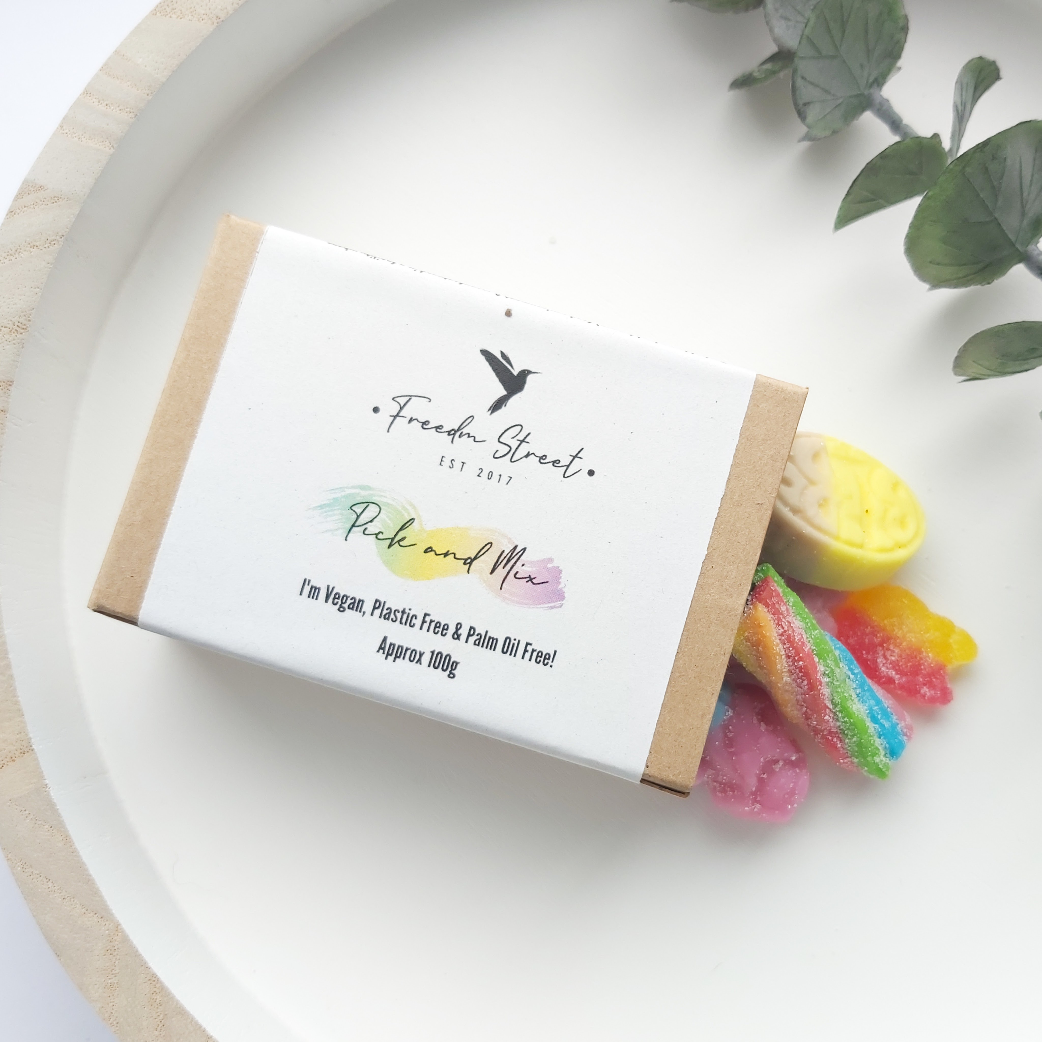 The small, brown, cardboard box with white label sits on a white, wooden round tray with a eucalyptus stem to the side with the vegan, palm-oil free pick & Mix sweets spilling out of one end - Freedm Street Subscription Beauty Box review by Beauty Folio