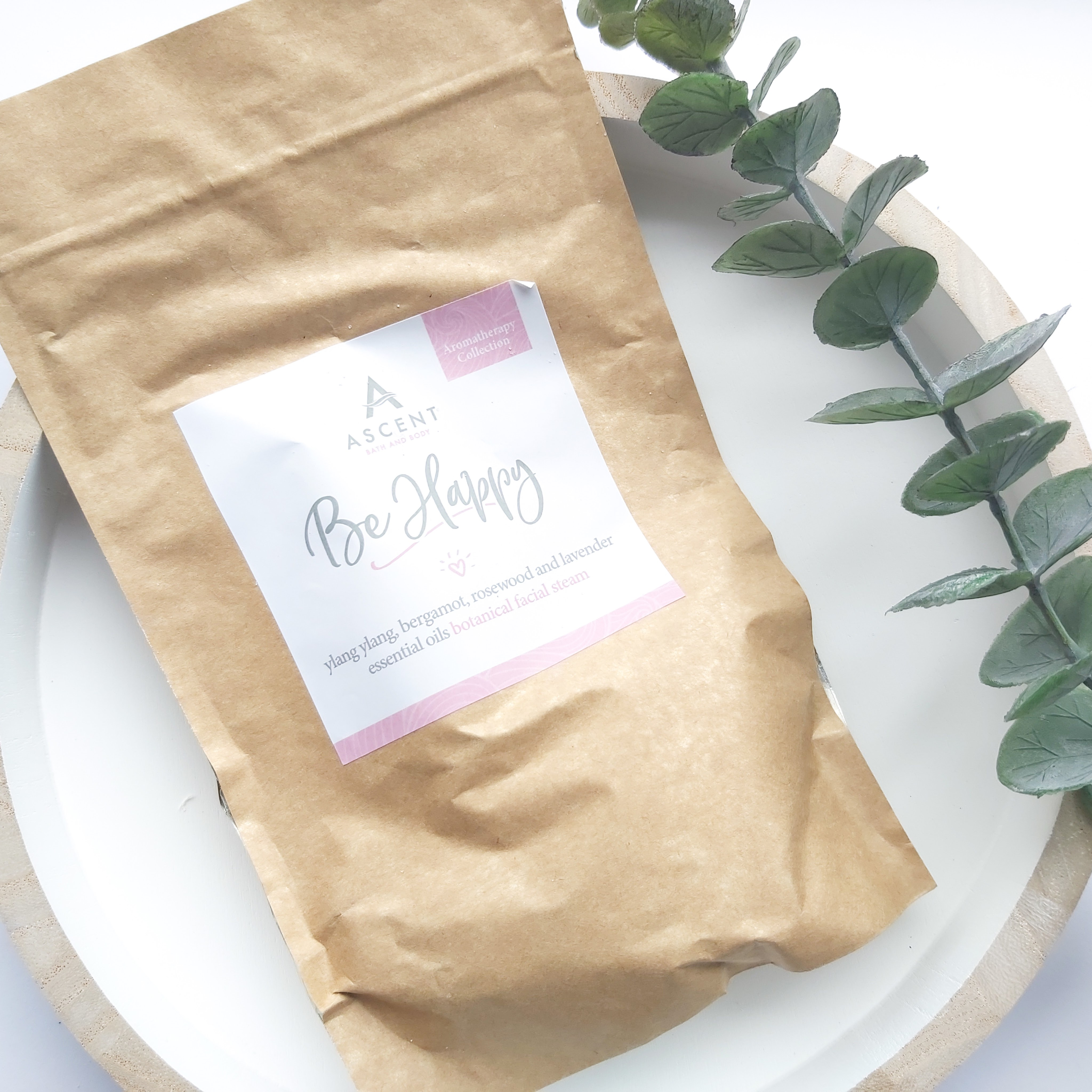 A brown pouch of facial steam sits on a white, wooden round tray with a eucalyptus stem to the side - Freedm Street Subscription Beauty Box review by Beauty Folio