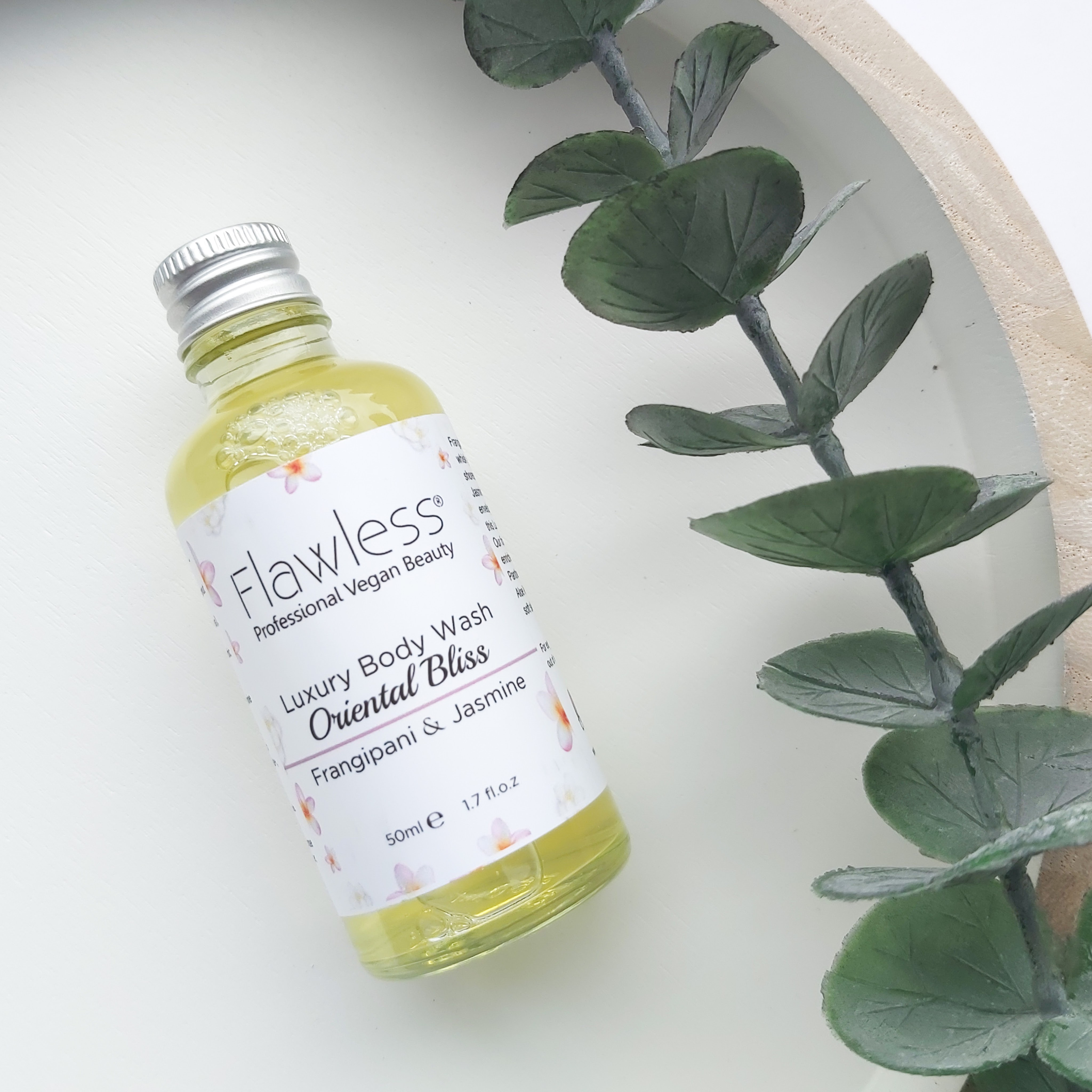 Flawless Oriental Bliss Luxury Body Wash comes in a clear bottle with silver lid and white labelling. It is laying on a white, wooden round tray with a eucalyptus stem to the side - Freedm Street Subscription Beauty Box review by Beauty Folio
