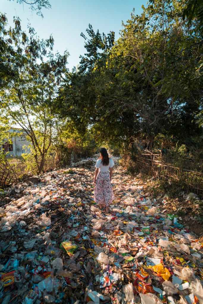 A woman walking over plastic waste. A Plastic Free Green Beauty Guide by Beauty Folio highlighting plastic pollution and plastic free beauty from Lovethical.