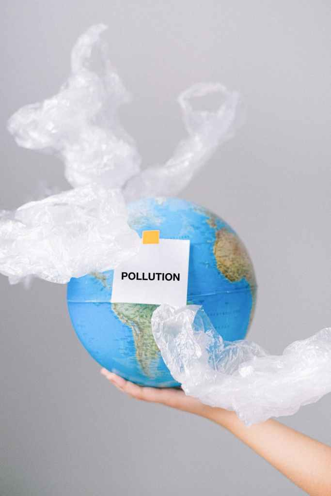The Earth wrapped in plastic with a sticker saying pollution. A Plastic Free Green Beauty Guide by Beauty Folio highlighting plastic pollution and plastic free beauty from Lovethical.