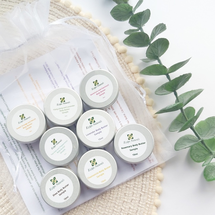 The full Ezape Naturals Body Butter Sample Bag with Organza bag on a beige pom pom placemat and bunch of eucalyptus - Review by Beauty Folio