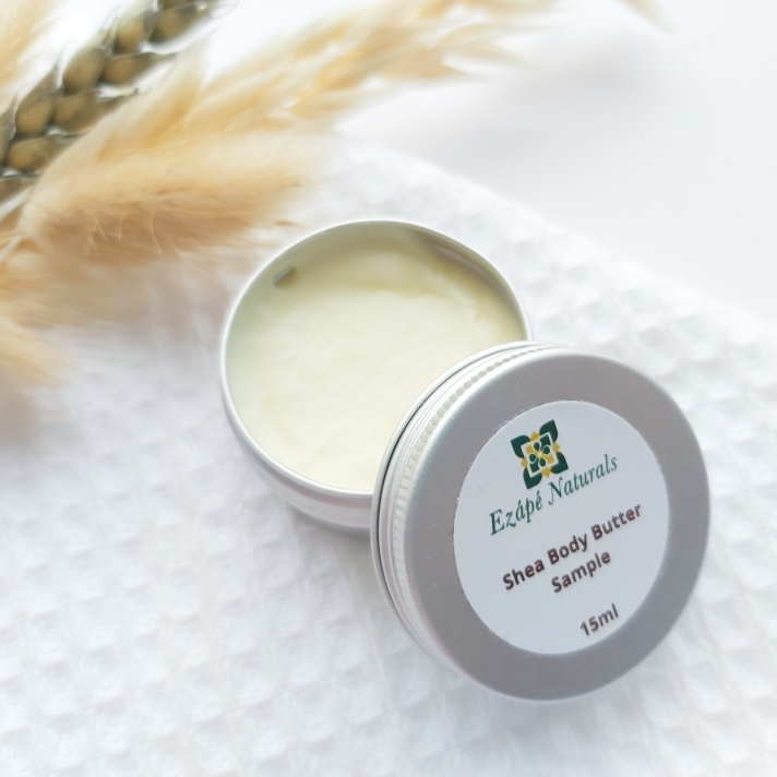 A 15ml tin of Ezape Naturals Shea Body Butter open on a white waffle flannel and spring of neutral dried flowers in the background. Review by Beauty Folio.