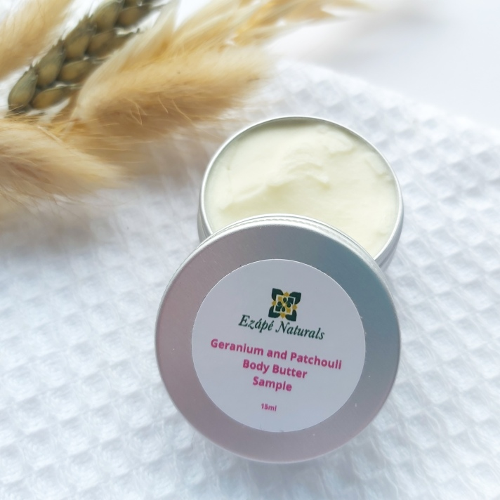 A 15ml tin of Ezape Naturals Geranium and Patchouli Body Butter open on a white waffle flannel and spring of neutral dried flowers in the background. Review by Beauty Folio.