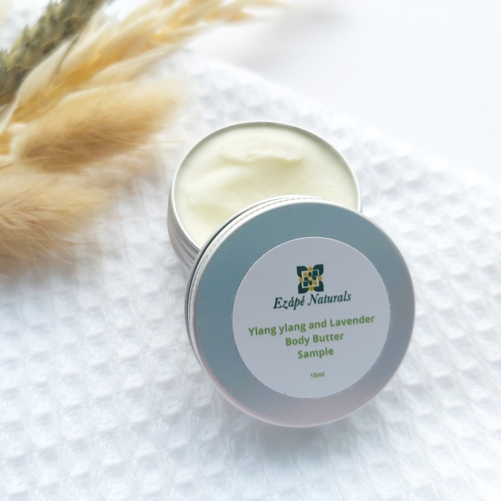 A 15ml tin of Ezape Naturals Ylang Ylang and Lavender Body Butter open on a white waffle flannel and spring of neutral dried flowers in the background. Review by Beauty Folio.