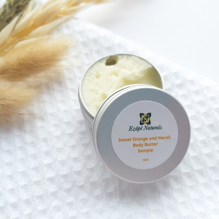 A 15ml tin of Ezape Naturals Sweet Orange and Neroli open on a white waffle flannel and spring of neutral dried flowers in the background. Review by Beauty Folio.