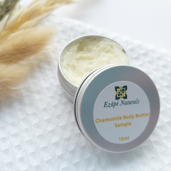 A 15ml tin of Ezape Naturals Chamomile Body Butter open on a white waffle flannel and spring of neutral dried flowers in the background. Review by Beauty Folio.