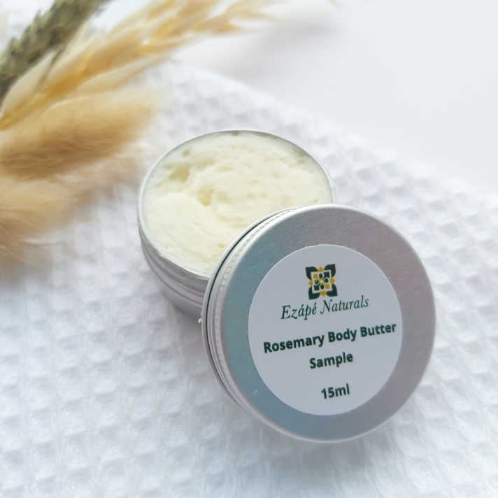A 15ml tin of Ezape Naturals Rosemary Body Butter open on a white waffle flannel and spring of neutral dried flowers in the background. Review by Beauty Folio.