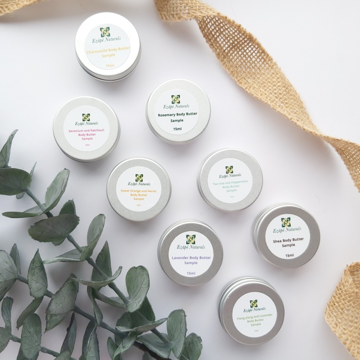 All 8 x 15ml tins of Ezape Naturals Body Butters from the Body Butter Sample Pack on a white background with jute ribbon curled on one side and a bunch of eucalyptus on the other. Review by Beauty Folio.