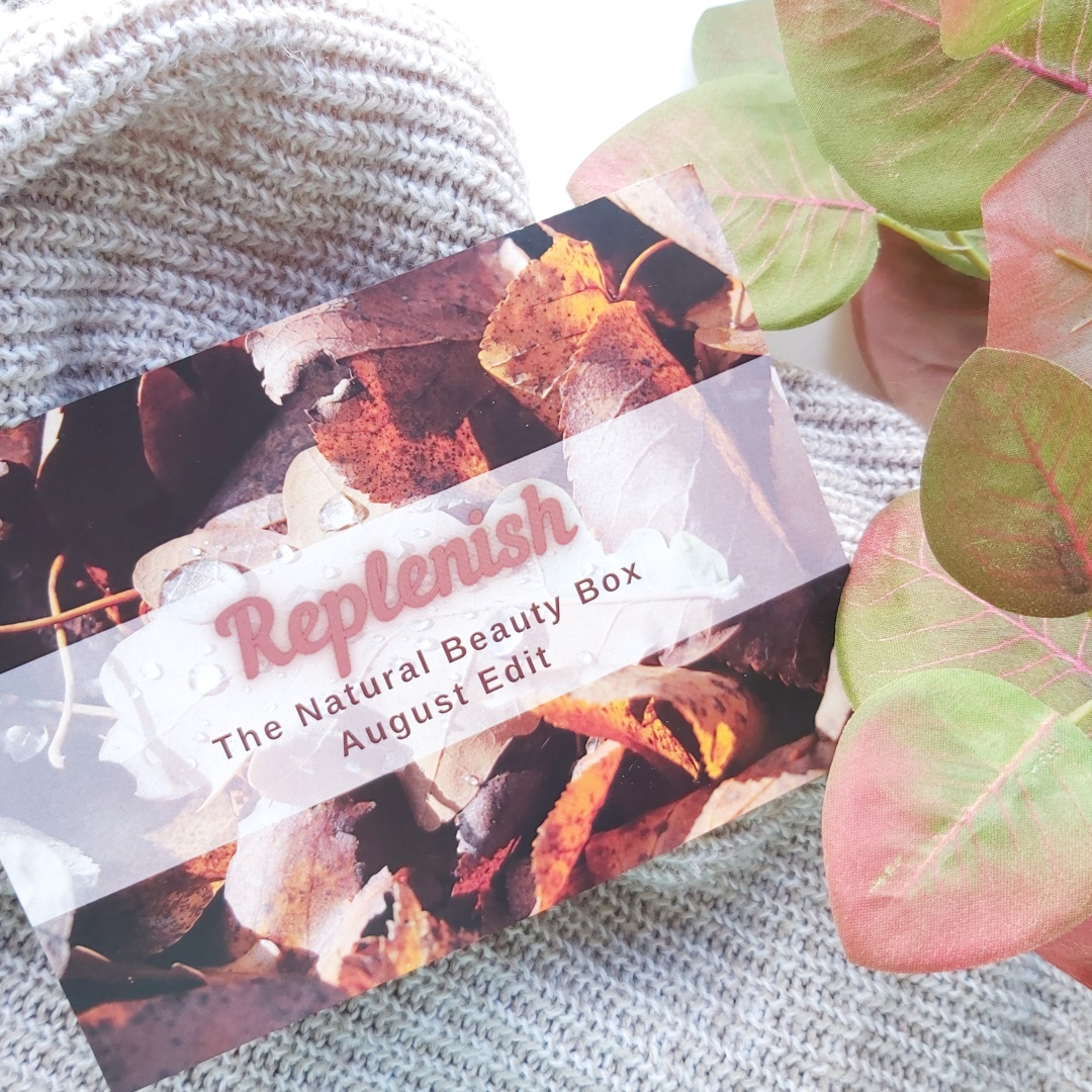 The Autumnal info card for The Natural Beauty Box laying on a knitted throw. Review by Beauty Folio